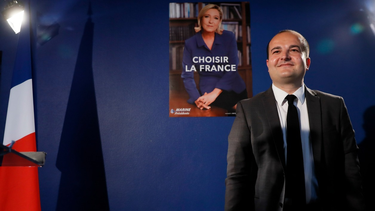 French far-right party Front National (FN) senator, Mayor of Frejus and FN presidential candidate Marine Le Pen's campaign director, David Rachline, stands next to the official campaign poster and the slogan for the second round of the election during a press conference for its presentation on April 26, 2017 in Paris.  Thomas SAMSON / AFP