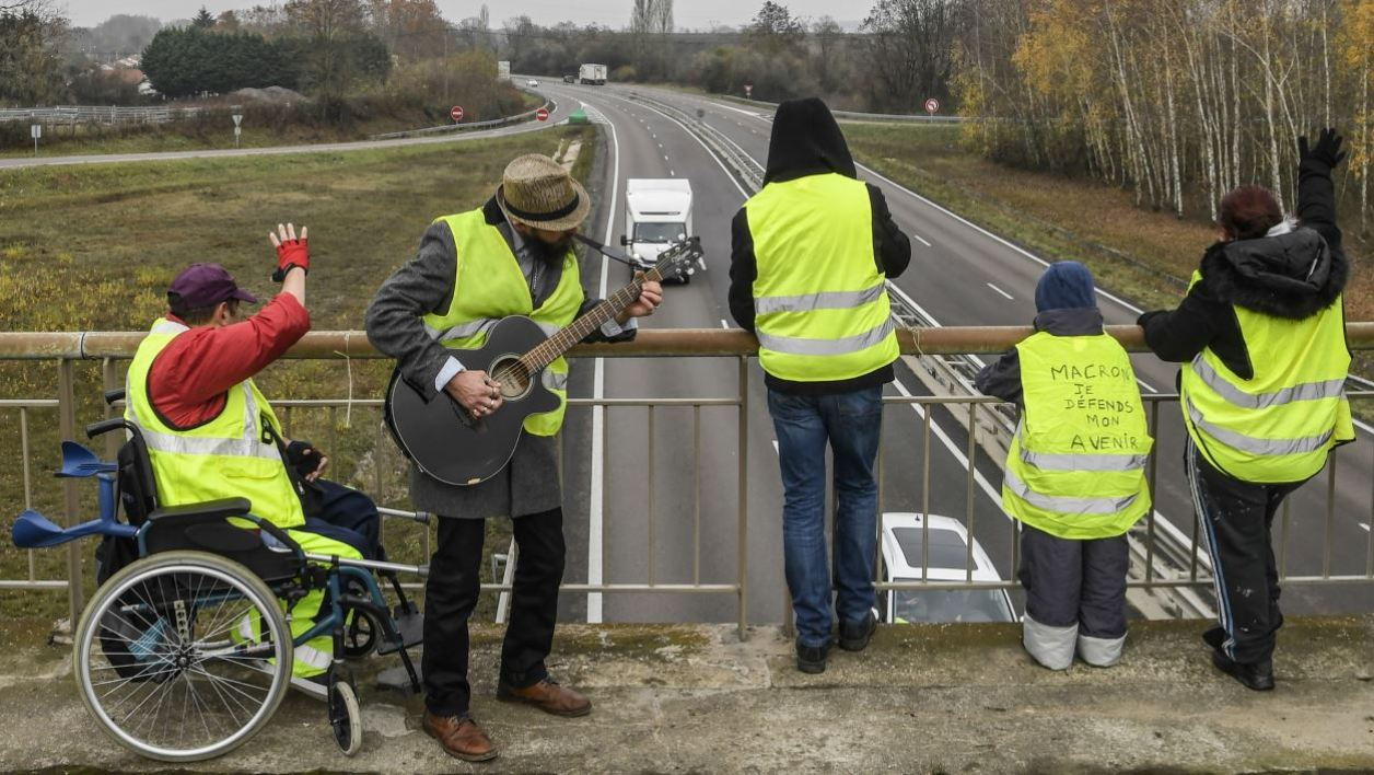 Protesters wearing yellow vests (gilets jaunes in French) stand on a bridge over the N70 road, on the fifth day of a movement against high fuel prices which has mushroomed into a widespread protest against stagnant spending power under French President on November 21, 2018, near Montceau-les-Mines, central France.  PHILIPPE DESMAZES / AFP