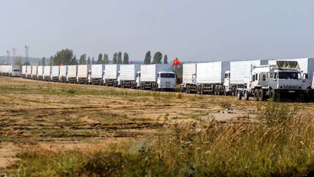 "RUSSIAN FEDERATION, Voronezh : Trucks of Russian humanitarian convoy wait at the location outside Voronezh some 400 km outside Moscow on August 13, 2014. A massive Russian aid convoy rumbled towards Ukraine's border on August 13 as Kiev vowed to block what it feared could be a ""Trojan horse"" bringing military assistance to pro-Kremlin rebels fighting a bloody insurgency in the east. Russian television images showed a line of nearly 300 lorries moving through the countryside, covered with white tarpaulin and stretching over almost three kilometres (two miles). AFP PHOTO / VLADIMIR BARYSHEV"
