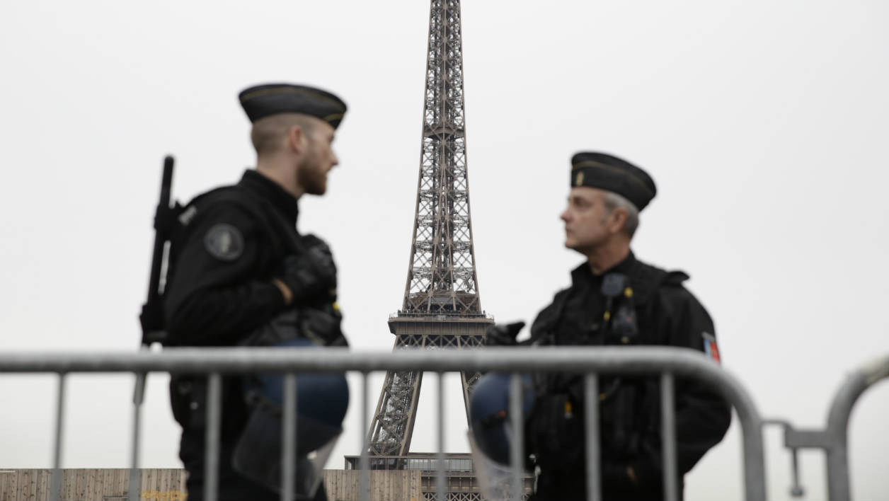The Eiffel Tower is seen in the background as French gendarmes, part of Operation Sentinelle, patrol near the Musee de l'Homme in Paris on April 14, 2016, where the French president is to take part in a TV question-and-answer session later in the evening. AFP PHOTO / KENZO TRIBOUILLARD