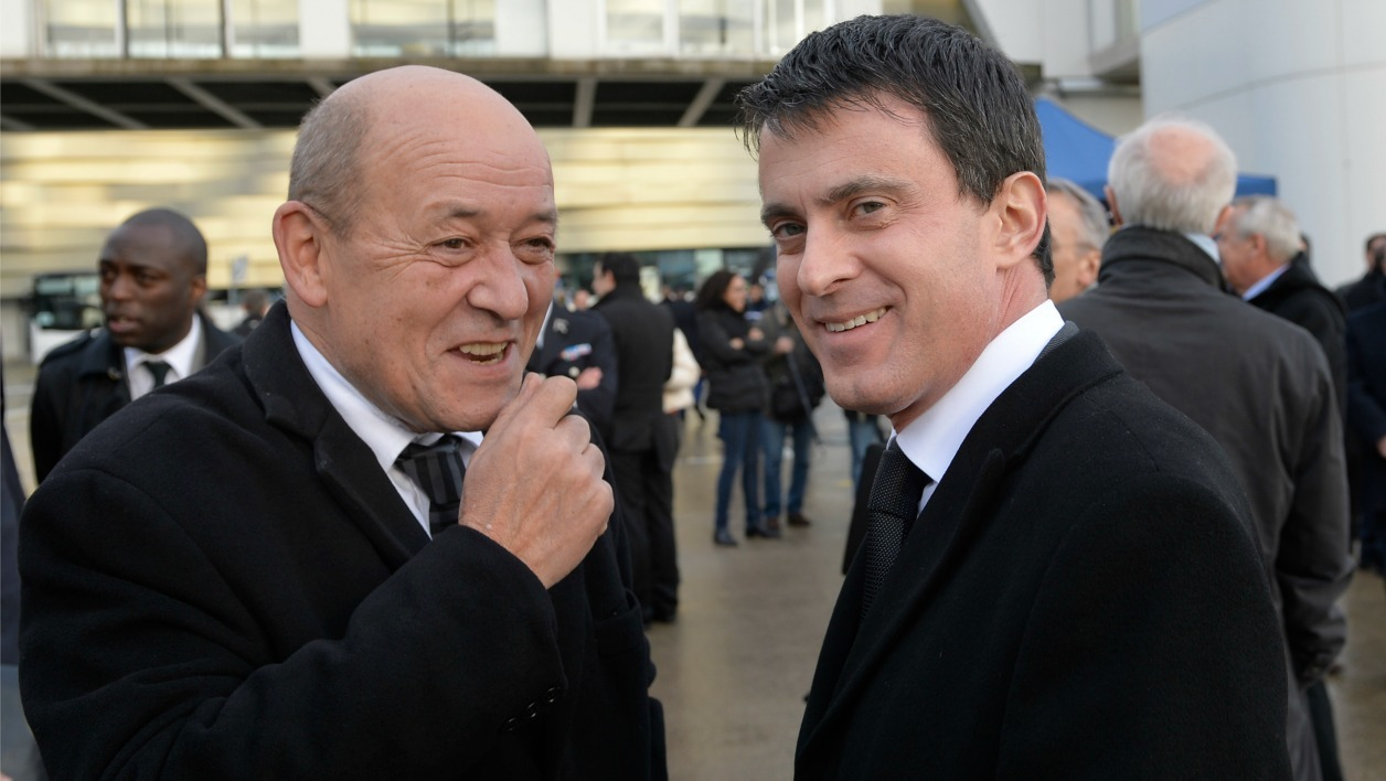 French Interior Minister Manuel Valls (C) speaks with French Defence Minister Jean-Yves Le Drian (L) as they visit the Roissy-Charles de Gaulle airport, in Roissy-en-France, outside Paris, on February 13, 2014, during a visit focused on the revamp of France's national security alert system Vigipirate. AFP PHOTO / ERIC FEFERBERG ERIC FEFERBERG / AFP