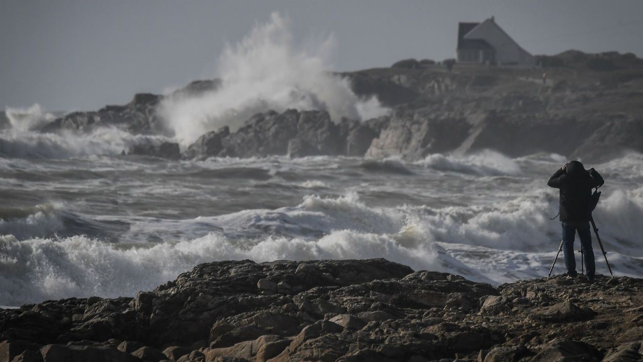 A man takes images of waves breaking on a pear on March 4, 2019 in Batz-sur-Mer, western France as violents winds generated by Freya storm hit northeastern France.  LOIC VENANCE / AFP