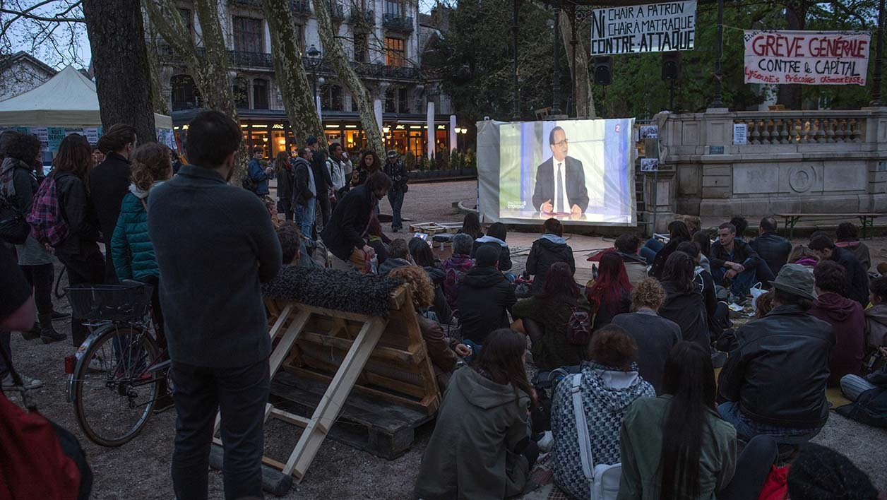 "People look at a TV broadcast of French President Francois Hollande attending a 90-minutes of questioning from a panel of journalists and four French voters during a programme called ""Dialogues Citoyens"" -""Citizen's Dialogue"" as they take part in the ""Nuit Debout"" (Up All Night) movement on the Place Granvelle in Besancon on April 14, 2016."