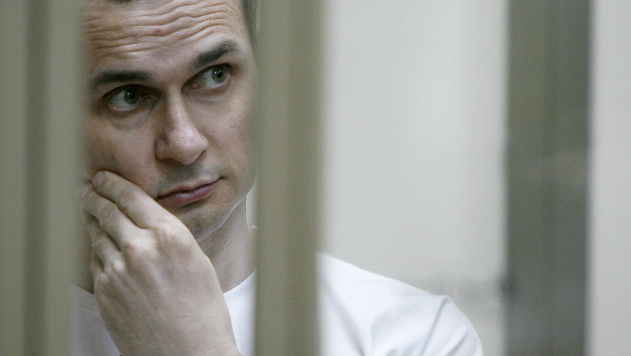 Ukrainian film director Oleg Sentsov stands inside a defendants' cage during a hearing at a military court in the city of Rostov-on-Don on July 21, 2015. A Ukrainian film director went on trial on terror charges in southern Russia on July 21, after Moscow held him for more than a year in a case decried by Kiev, rights groups and prominent film directors across the globe. AFP PHOTO / SERGEI VENYAVSKY