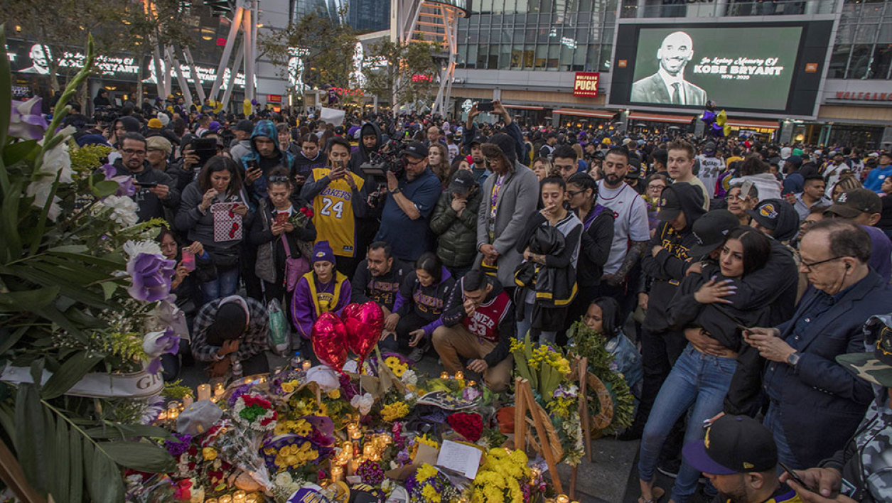 People gather around a makeshift memorial for former NBA and Los Angeles Lakers player Kobe Bryant after learning of his death, at LA Live plaza in front of Staples Center in Los Angeles on January 26, 2020.