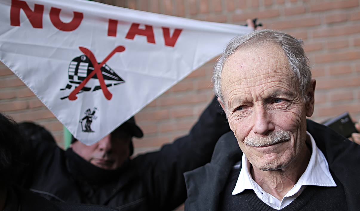"""In this file picture shows a supporter (L) of Italian writer Erri De Luca (R) holding a banner """"No Tav"""" (Tav, means high-speed train) on January 28, 2015 outside the courthouse in Turin. Erri de Luca was sent to trial for saying an environmentally controversial train link should be """"sabotaged"""" and plans to make freedom of expression the centre of his defence. Italian prosecutors called for Erri de Luca to be thrown behind bars for eight months and the verdict is expected on October 19, 2015"""