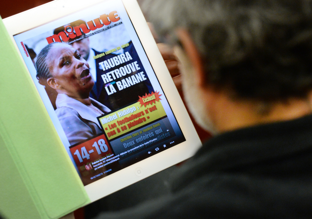 "FRANCE, Paris : A man who participates in a political debate, on November 12, 2013, in a room of the National Assembly in Paris, looks at a reproduction of the front page of French far-right weekly magazine ""Minute"" with a picture of French Justice Minister Christiane Taubira entitled ""Maligne comme un singe, Christiane Taubira retrouve la banane"" (""Clever as a monkey, Taubira gets her bounce back""). The magazine headlined on its November 13, 2013 issue this sentence as repeated racial slurs have recently targeted the Minister of Justice. The debate, attended by Christiane Taubira, and entitled ""Face a la montee du Front National, quelles reponses la gauche doit-elle apporter ?"" (To face the rise of Front national, how the Left could answer ?) is initiated by ""La Gauche Forte"" (Strong Left, a political movement). The FN is a far-right French party. AFP PHOTO PIERRE ANDRIEU"