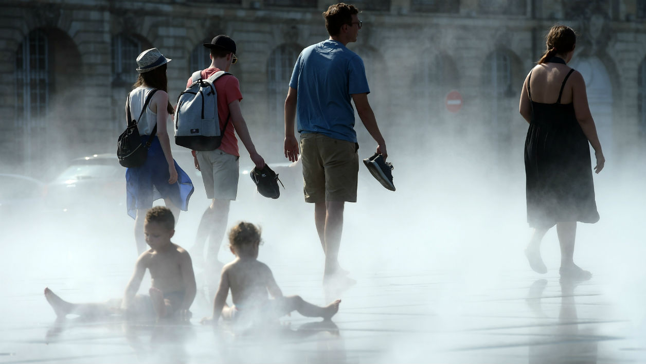People cool off at the water mirror fountain, whose system alternates a mirror effect with a mist effect, on June 19, 2017 in Bordeaux's city center, southwestern France. French national meteorological service, Meteo France has placed 16 departments on orange alert for heatwaves, with temperatures between 33°C et 38°C expected in the Paris region and southwestern France. NICOLAS TUCAT / AF