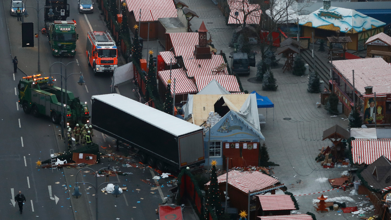 "A truck is towed away on December 20, 2016 as forensic experts examine the scene around a truck that crashed into a Christmas market near the Kaiser-Wilhelm-Gedaechtniskirche (Kaiser Wilhelm Memorial Church) in Berlin. German police said they were treating as ""a probable terrorist attack"" the killing of 12 people when the speeding lorry cut a bloody swath through the packed Berlin Christmas market. Odd ANDERSEN / AFP"