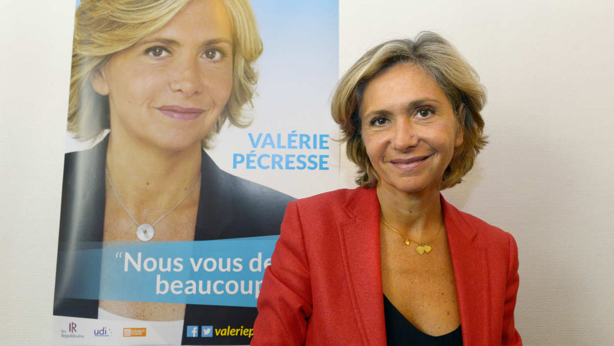 Valerie Pecresse, Les Republicains right-wing party's candidate for the December regional elections in Ile-de-France, poses next to her campaign poster on September 18, 2015 in Paris. The regional elections will take place on December 6 and 13, 2015. AFP PHOTO / BERTRAND GUAY