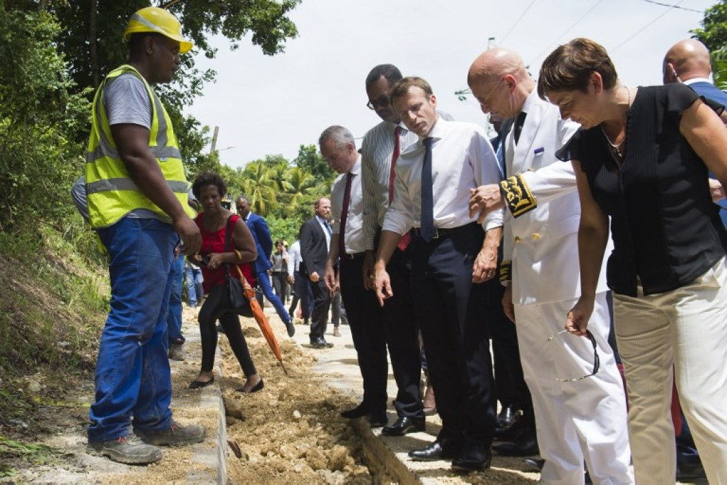 "French President Emmanuel Macron (3rdR), flanked by French Minister for the Ecological and Inclusive Transition Francois de Rugy (5thR) and French Overseas Minister Annick Girardin stand at a construction site during a visit on the theme of water and the problem of ""water holes"" (dilapidated pipes) after he visits a pipeline change site in the ""Les Grands Fonds - les Abymes"" district in the suburb of Point à Pitre, Guadeloupe, on September 28, 2018, during a trip with French President in the French West Indies, one year after Hurricane Maria damaged the Island.  Eliot BLONDET / POOL / AFP"