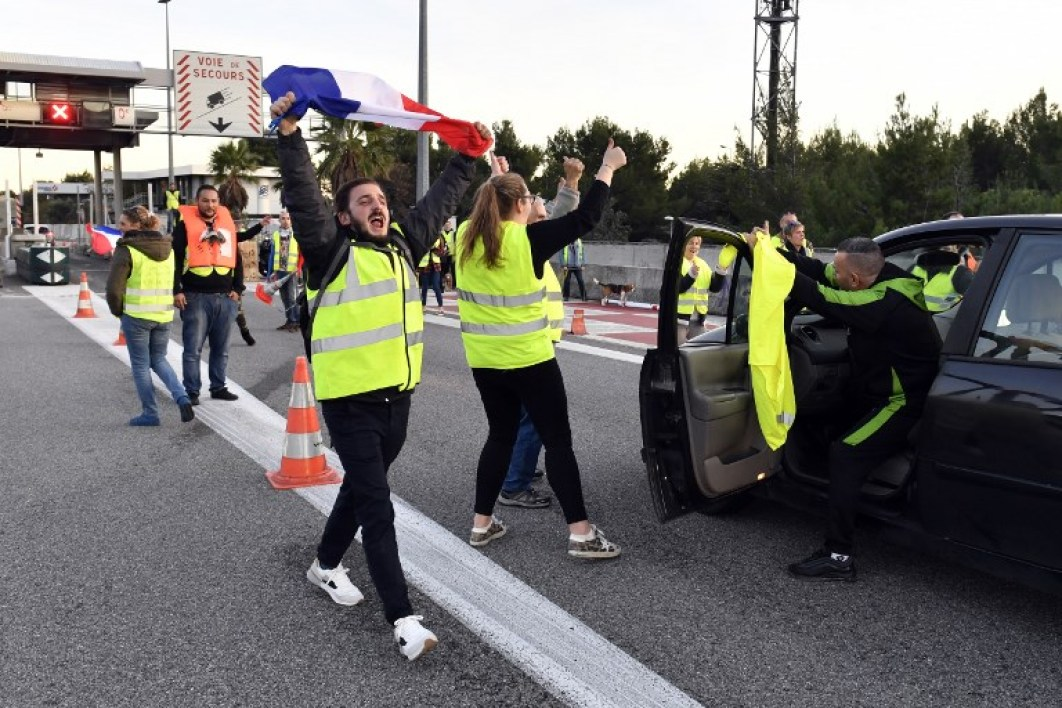 "Yellow vest (gilet jaune) protesters take part in a blockade of a toll in La Ciotat near Marseille, southern France on December 1, 2018. Across the country some 36,000 people took part in mainly peaceful protests against a surge in fuel prices this year, which they attribute to a series of tax increases to finance the government's anti-pollution efforts. The ""yellow vest"" movement erupted on social media in October 2018 and has since become a wider protest against Macron, who is accused of failing to recognise the rising costs of living that has left many struggling. GERARD JULIEN / AFP"