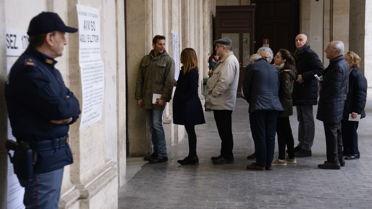 People queue to vote during a referendum on constitutional reforms, on December 4, 2016 outside a polling station in Rome. Italians began voting today in a constitutional referendum on which reformist Prime Minister Matteo Renzi has staked his future.