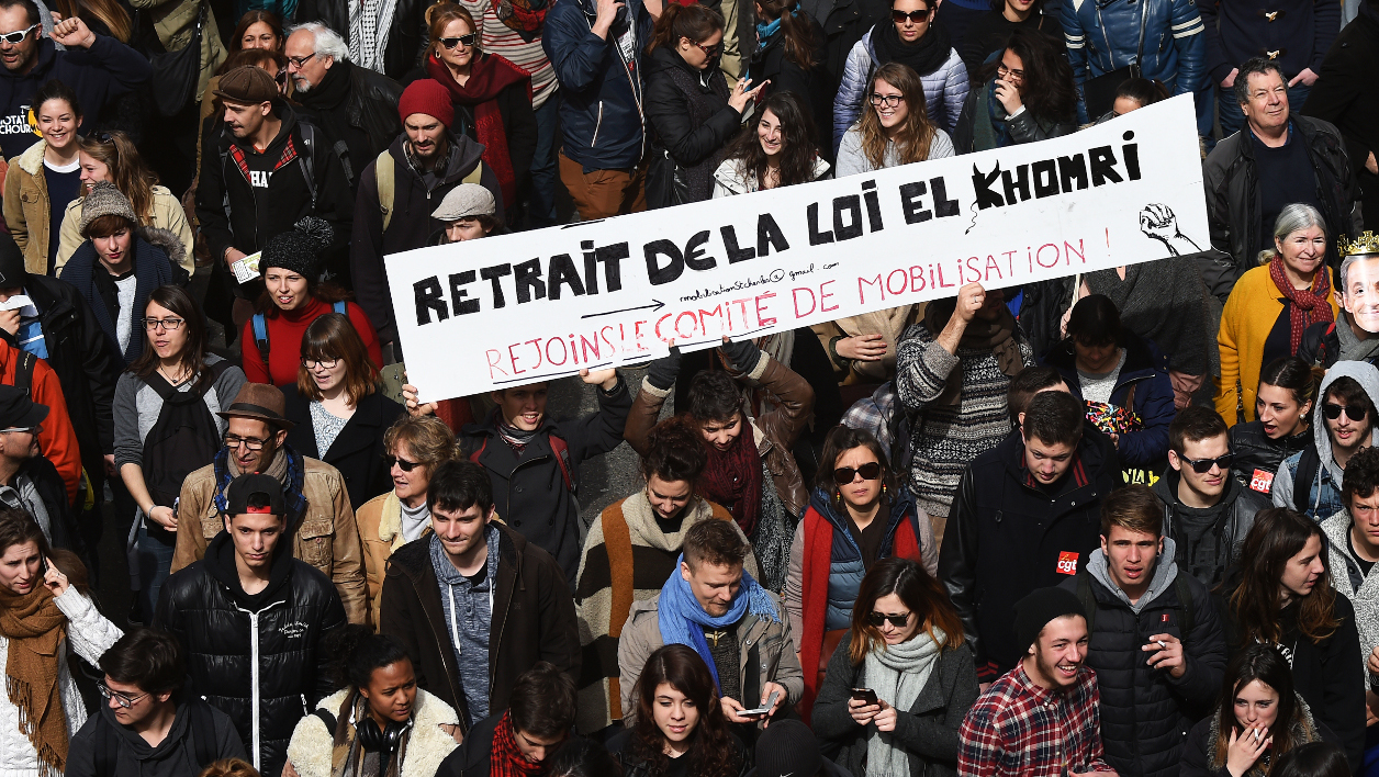 "People hold a cardboard reading ""Withdrawal of the El Khomri law - Join the mobilization committee"" as they take part in a nationwide day of protest against deeply unpopular labour reforms that have divided the Socialist government and raised hackles in a country accustomed to iron-clad job security, on March 9, 2016 in Marseille, southern France. France's government has faced massive blowback -- including from within its ranks -- to measures that would give bosses more flexibility in hiring and firing. ANNE-CHRISTINE POUJOULAT / AFP"