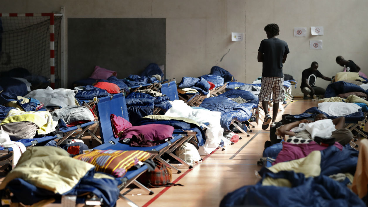 A migrant walks past folding beds in a gymnasium on August 22, 2017 at a camp set up at the Physical Education Institute, the sports campus of the Pantheon-Assas University in Paris.  PATRICK KOVARIK / AFP