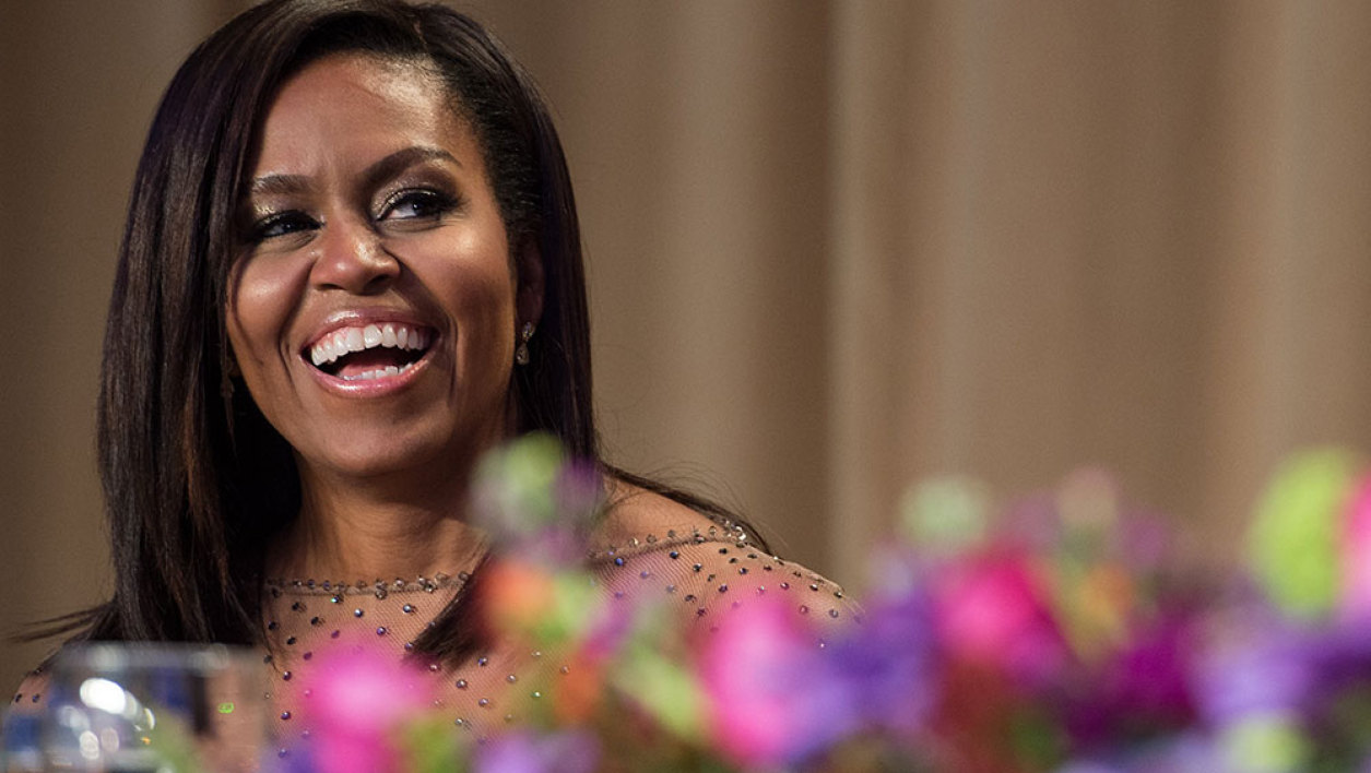 US First Lady Michelle Obama laughs at a joke by her husband President Barack Obama during the 102nd White House Correspondents' Association Dinner in Washington, DC, on April 30, 2016.