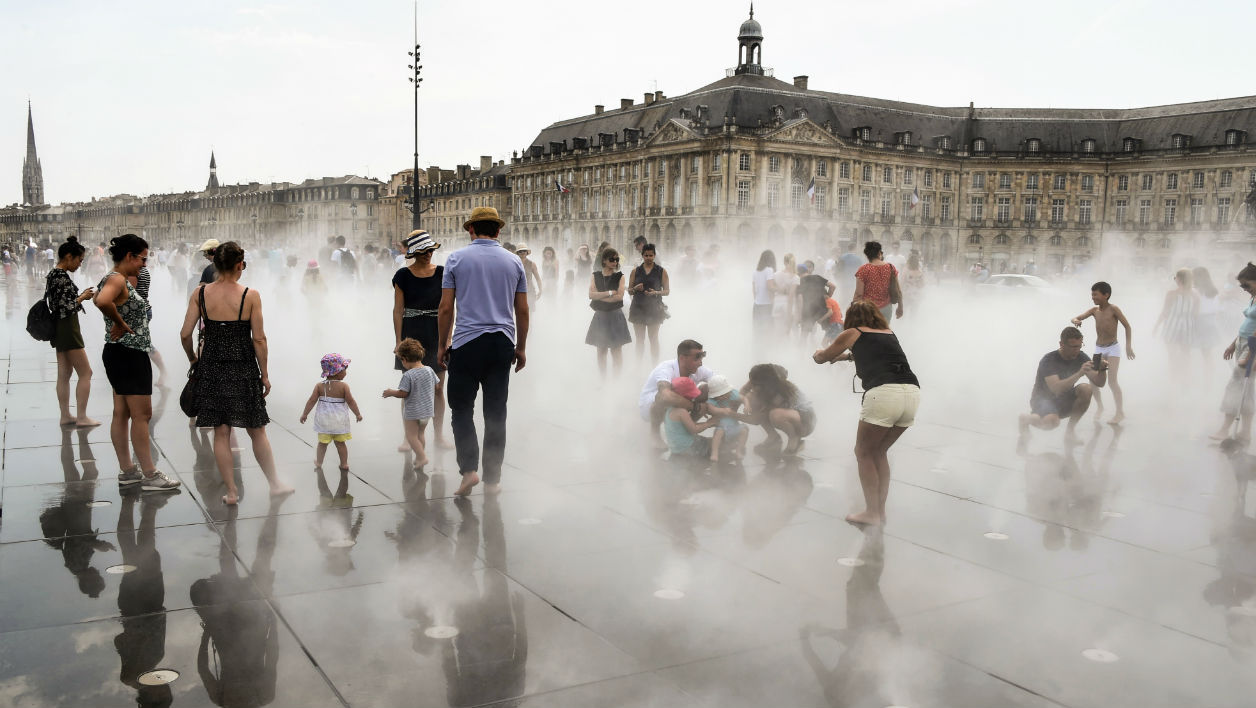 "People cool themselves in the ""miroir d'eau"" (water miror) fountain in Bordeaux's city center on May 27, 2017.  MEHDI FEDOUACH / AFP"