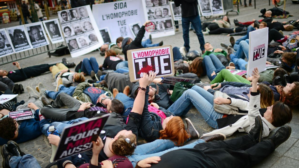 "People hold placards during a sit-in protest called by Act Up gay organisation in front of a ""Wall of homophobs"" displaying portraits of national and international public personnalities stamped by the organisation as homophobic on May 17, 2013 in Paris, as part of the International Day Against Homophobia and Transphobia."