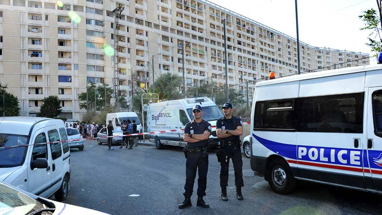 Policemen stand guard at the Lauriers residence where a 25 year old man was killed by a burst of Kalashnikov rifle fire, in the 13th arrondissement of Marseille, on July 29, 2012, according to sources close to the investigation. The source said the man was chased by a pickup truck before being shot at and the police are investigating. AFP PHOTO / ANNE-CHRISTINE POUJOULAT