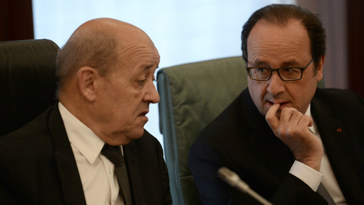 French President Francois Hollande(R) talks with French Defense minister Jean-Yves Le Drian (L) during a meeting with Nigerian President at the Presidential Palace in Abuja on May 14, 2016. Regional and Western powers gathered in Nigeria today for talks on quelling the threat from Boko Haram as the UN warned of the militants' threat to African security and ties to the Islamic State group. STEPHANE DE SAKUTIN / POOL / AFP