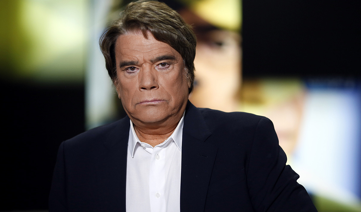 Embattled tycoon Bernard Tapie poses before a broadcasted debate on French news channel iTele on July 10, 2013 in Paris, as French investigators have ordered today some of his assets seized as part of a corruption probe linked with IMF chief. Tapie has been charged with organised fraud in the probe, which relates to a 400 million euro ($525 million) state payout Tapie received in 2008 when Christine Lagarde was France's finance minister.