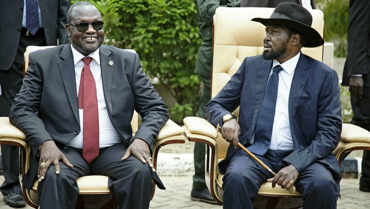 First Vice President of South Sudan and former rebel leader, Riek Machar (L), and President Salva Kiir (R), sit for an official photo with the 30 members of the new cabinet of the Transitional Government at the Cabinet Affairs Ministry, in Juba on April 29, 2016. The new cabinet of the Transitional Government includes former rebels and members of the opposition, a step forward in a drawn-out peace process aimed at ending more than two years of conflict.
