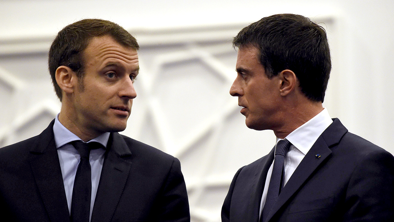 French Prime minister Manuel Valls (R) talks with his Economy and Industry Minister Emmanuel Macron during the opening of the 3rd forum on partnerships between France and Algeria on April 10, 2016 in the capital Algiers.