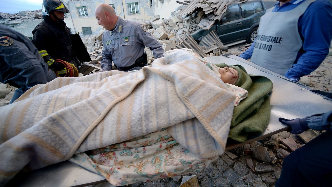 Rescues carry a man in Amatrice on August 24, 2016 after a strong heartquake. Central Italy was struck by a powerful, 6.2-magnitude earthquake in the early hours of Wednesday, which has killed at least three people and devastated dozens of mountain villages.