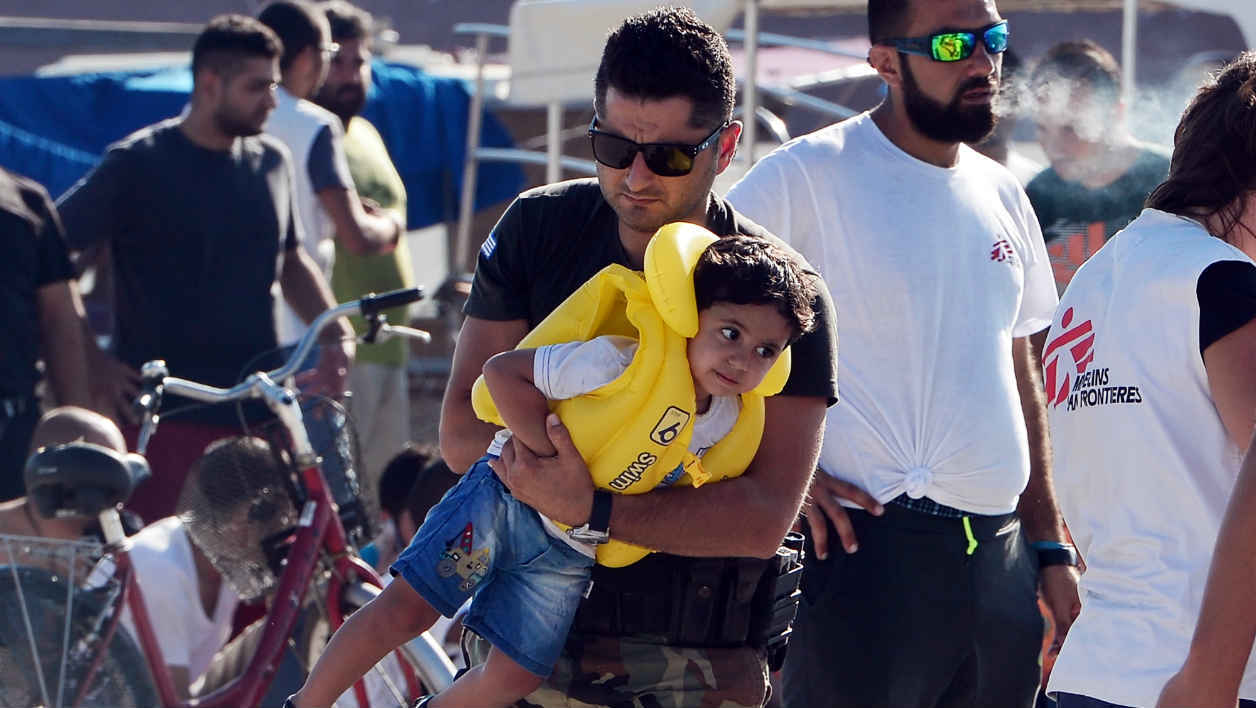 A Greek coast guard carries a migrant child at the port of Kos, after intercepting a group of migrants at sea between Greece and Turkey, off Kos island on August 18 , 2015. Authorities on the island of Kos have been so overwhelmed that the government sent a ferry to serve as a temporary centre to issue travel documents to Syrian refugees -- among some 7,000 migrants stranded on the island of about 30,000 people. The early hours are the safest time for migrants travelling from Turkey to the Greek islands just across the water, which have seen a huge influx of refugees escaping the civil war in Syria and chaos in Afghanistan since the beginning of this year. AFP PHOTO /LOUISA GOULIAMAKI