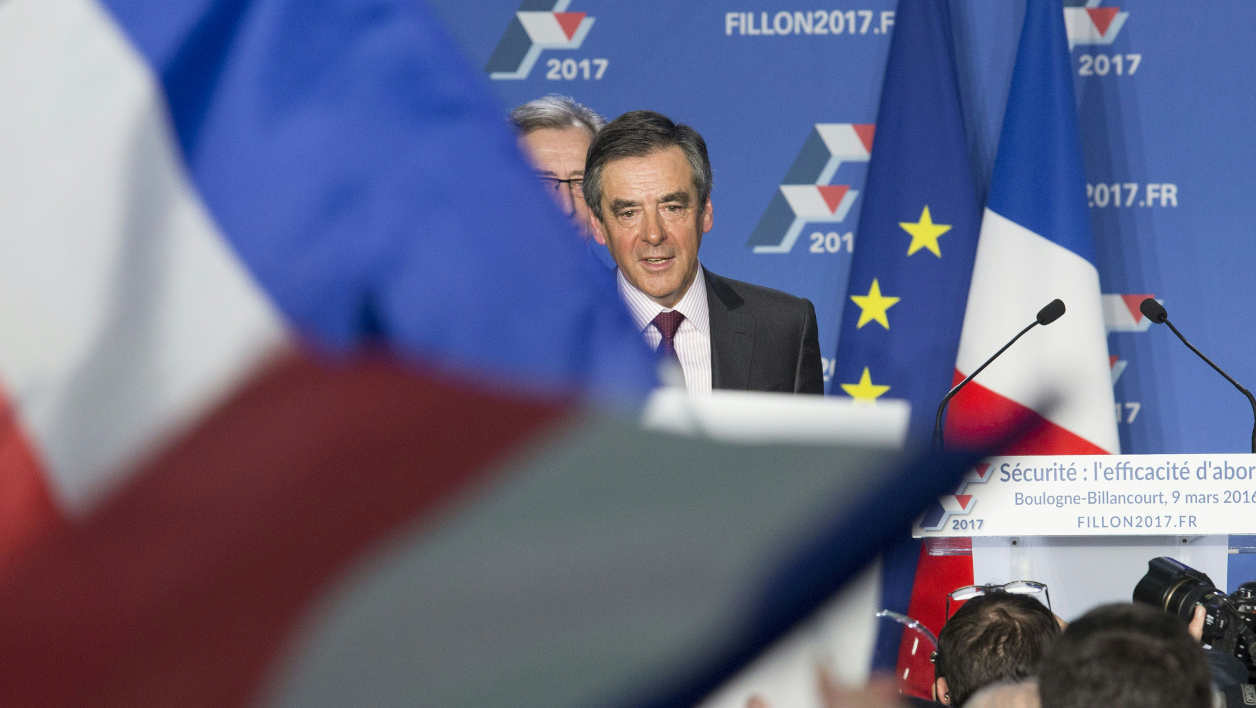 """Former French Prime Minister and right-wing Les Republicains (LR) parliament member Francois Fillon (C) sings the French National anthem """"La Marseillaise"""" with his team at the end of a meeting entitled 'Security in France - Crime, Delinquency, Terrorism' in Boulogne-Billancourt, west of Paris, on March 9, 2016.  Geoffroy Van der Hasselt / AFP"""
