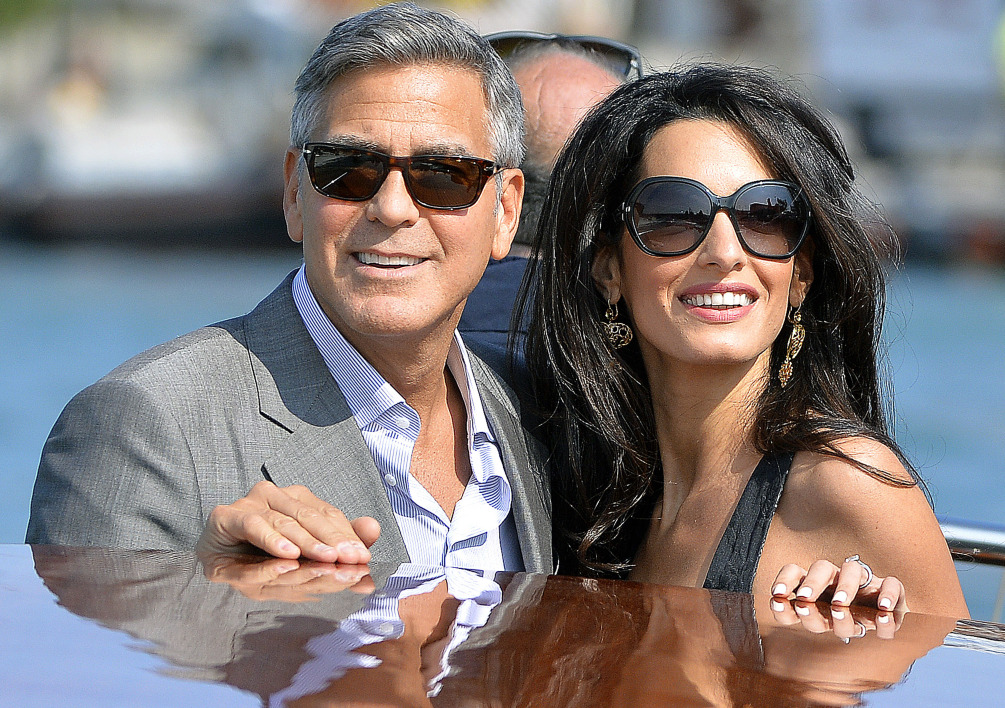 ITALY, Venice : TOPSHOTS US actor George Clooney ( L) and his Lebanon-born British fiancee Amal Alamuddin take a taxiboat upon their arrival in Venice on September 26, 2014, on the eve of their wedding. AFP PHOTO / ANDREAS SOLARO
