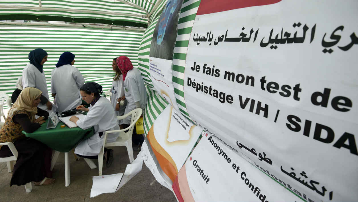 Algerian people get tested for HIV by health workers at a mobile centre in the capital Algiers on June 11, 2015 during an operation for the prevention of AIDS organised by the United Nations Programme on HIV/AIDS (UNAIDS) offices in Algiers. AFP PHOTO / FAROUK BATICHE