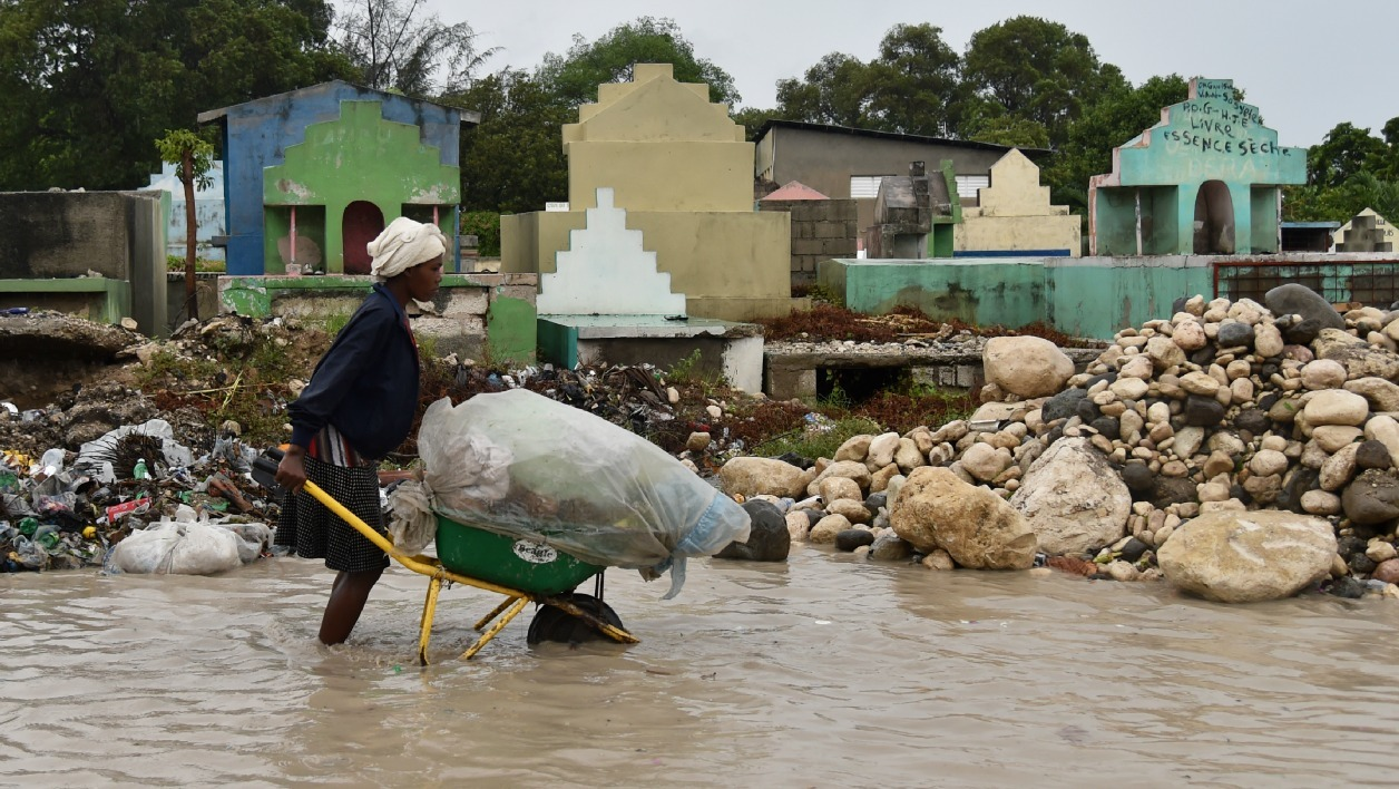 A woman pushes a wheelbarrow while walking in a partially flooded street, in the Haitian capital, Port-au-Prince, on October 4, 2016. Hurricane Matthew made landfall in southwestern Haiti early Tuesday, crashing ashore as a powerful Category Four storm, US weather forecasters said.