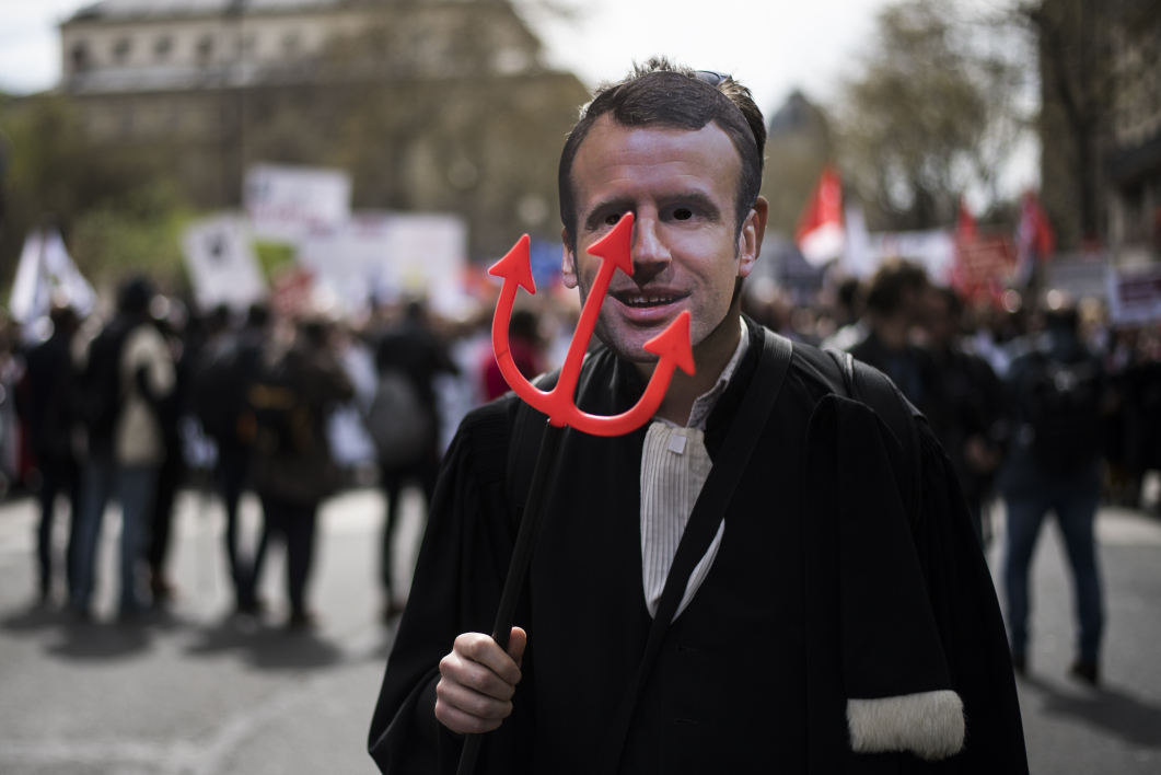 A man, with a mask featuring French President, takes part in a demonstration as part of a nation-wide action day by magistrates against a draft law to reform French justice system, on April 11, 2018 in Paris.  Lionel BONAVENTURE / AFP