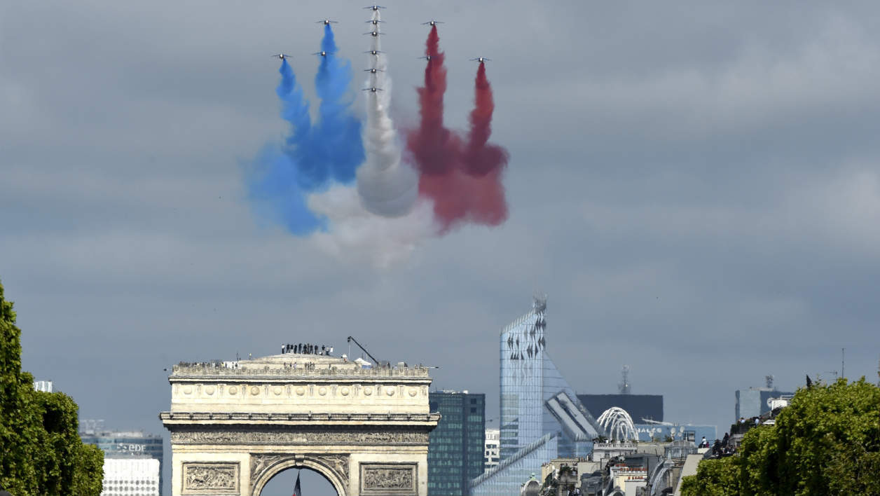 Alpha Jets of the French Air Force, La Patrouille de France, releasing trails of blue, white and red smoke in the colours of the French national flag fly over the Champs Elysees during the annual Bastille Day military parade in Paris on July 14, 2015. AFP PHOTO / ALAIN JOCARD