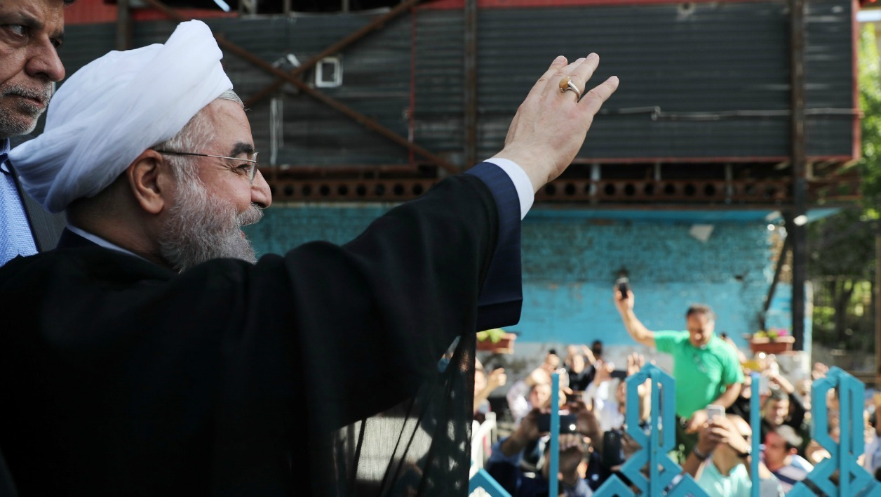 A handout picture released by the website of the Iranian President Hassan Rouhani on May 19, 2017, shows him waving to the crowd at a polling station in Tehran during the presidential elections.