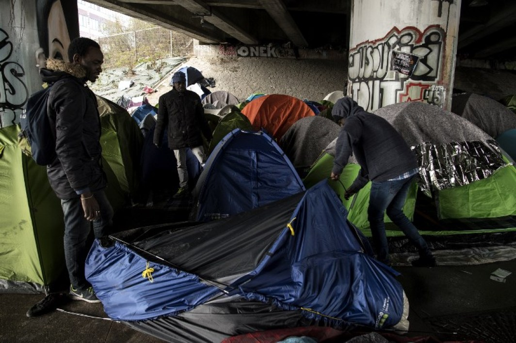 Migrants set up a tent at a makeshift camp set under a bridge along the canal de Saint-Denis in Paris on March 29, 2018.