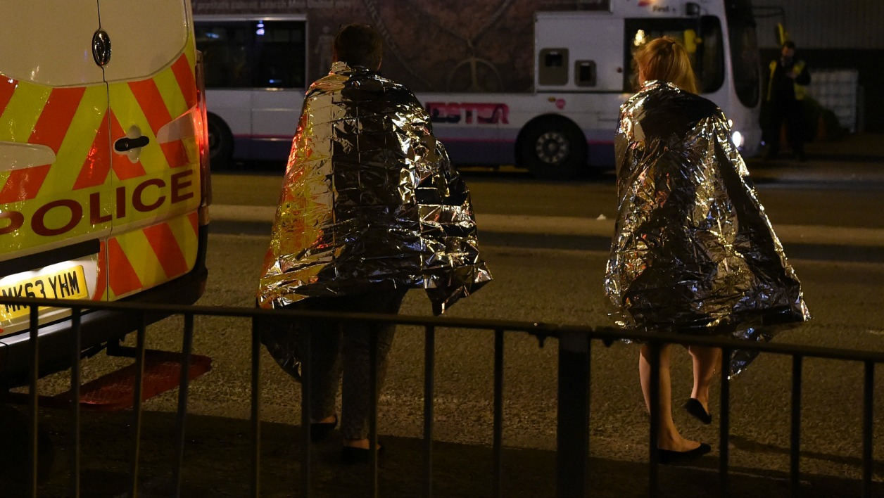 Concert goers wait to be picked up at the scene of a suspected terrorist attack during a pop concert by US star Ariana Grande in Manchester, northwest England on May 23, 2017.  PAUL ELLIS / AFP