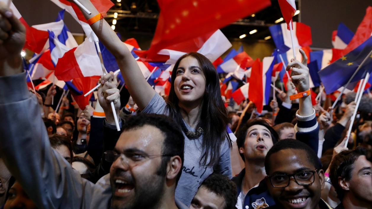 Supporters of French presidential election candidate for the En Marche ! movement Emmanuel Macron cheer following the announcement that he was on course to qualify for the run-off in France's presidential election in Paris on April 23, 2017. Far-right leader Marine Le Pen and centrist Emmanuel Macron were on course to qualify for the runoff in France's presidential election, initial projections suggested.