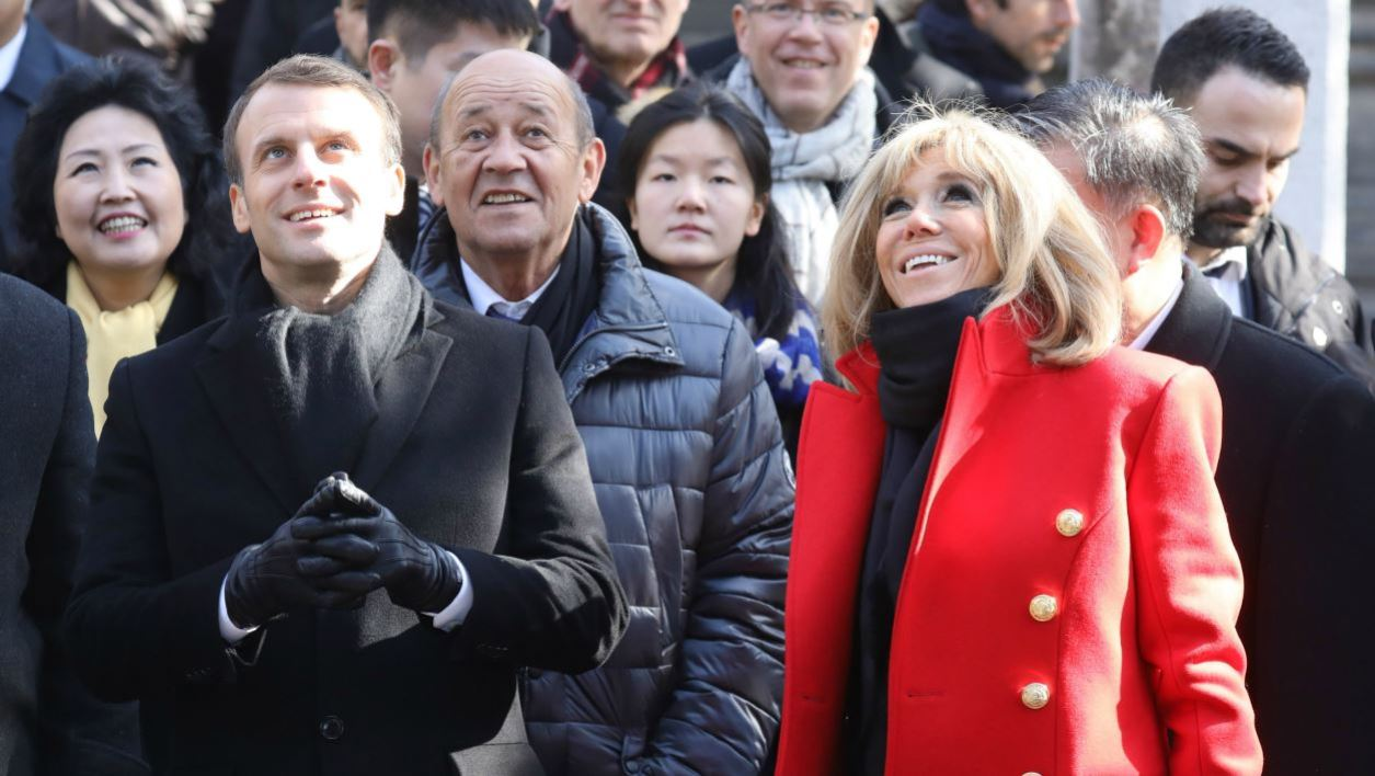 French President Emmanuel Macron (centre L) and his wife Brigitte Macron (centre R-red coat) are given a tour during a visit to the Great Mosque of Xian in the northern Chinese city of Xian on January 8, 2018. Macron on January 8 launched a state visit to China in Xian -- the starting point of the ancient Silk Road -- in a nod to his counterpart's scheme to revive the famous trading route. LUDOVIC MARIN / POOL / AFP