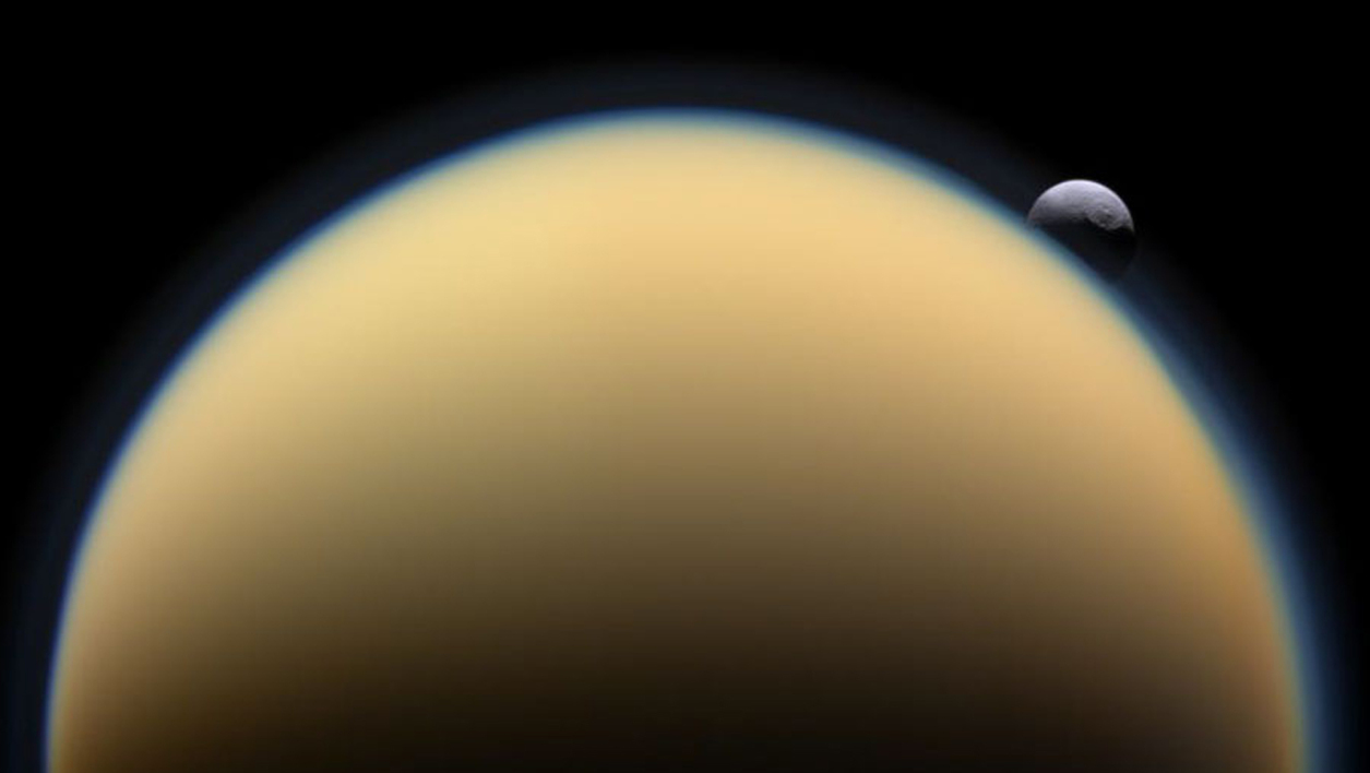 This NASA image received January 27, 2010 shows the heavily cratered Saturn moon Tethys slipping behind Saturn's atmosphere-shrouded Titan in 2009 captured by the robotic Cassini spacecraft orbiting Saturn.