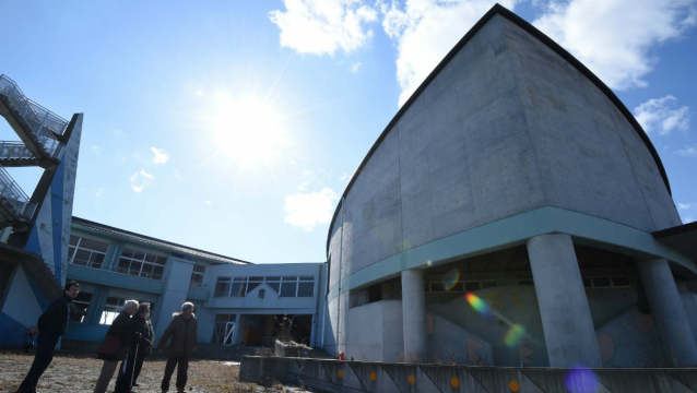 """Participants of """"dark tourism"""" look at abandoned Ukedo Elementary School in Namie, Fukushima Prefecture, after tsunami disaster and accident of Fukushima nuclear plant on February 11, 2016. As the fifth anniversary of the disaster approaches, a growing number of visitors are joining Fukushima-related tours. AFP PHOTO / Toru YAMANAKA TORU YAMANAKA / AFP"""